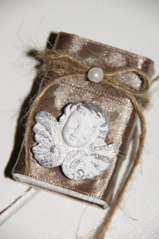 Brukte et brunt silkebånd i 3 omganger rundt, en engel, jutetråd i en sløyfe med en perle på.